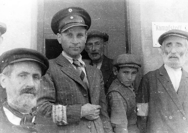 Tomaszow Mazowiecki a ghetto policeman stands with Jews